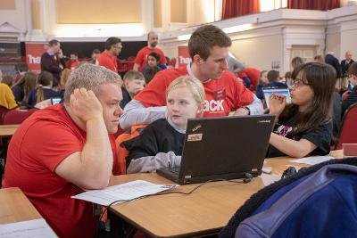 image of 2 children on laptops being supported by a mentor